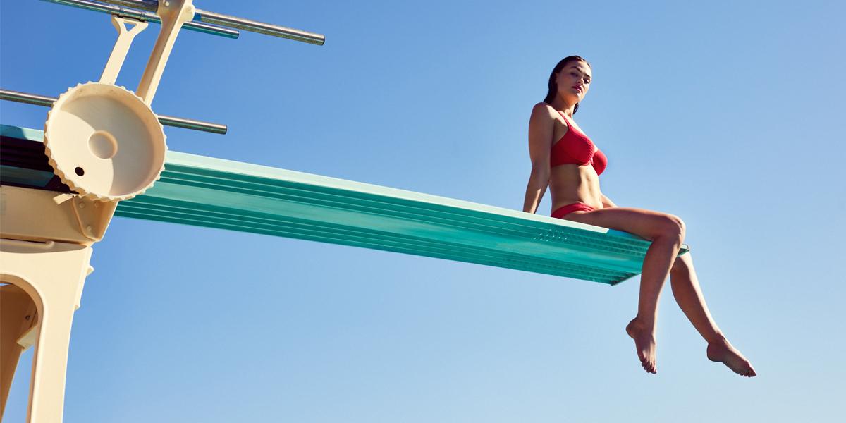 frau auf sprungbrett in bikini