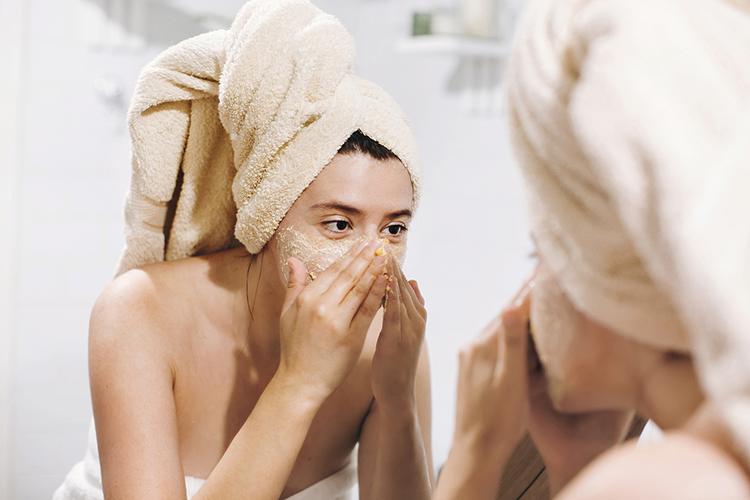 frau macht ein peeling vor badezimmer-spiegel