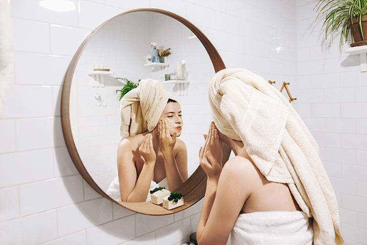 frau vor spiegel in badezimmer