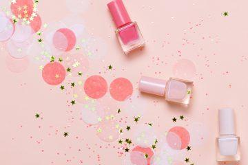 drei nagellacke auf rosa unterlage mit konfetti