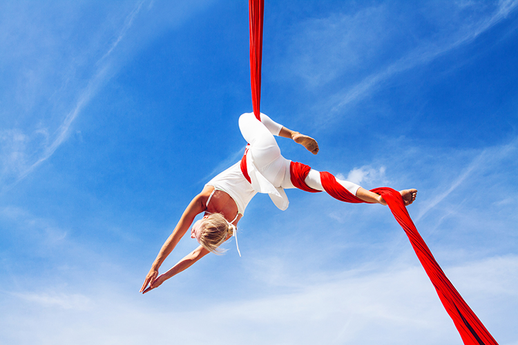 frau vor blauem himmel trainiert aerial yoga