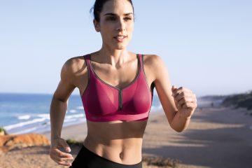 frau trägt sport-bh beim joggen am strand