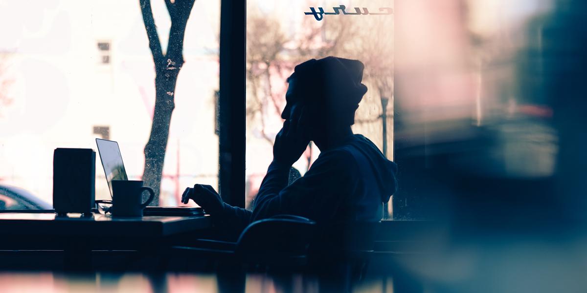 schattenspiel eines mannes in einem cafe vor einem laptop