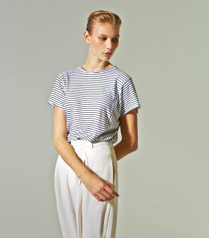 junge frau mit gestrieftem t-shirt und weißer hose