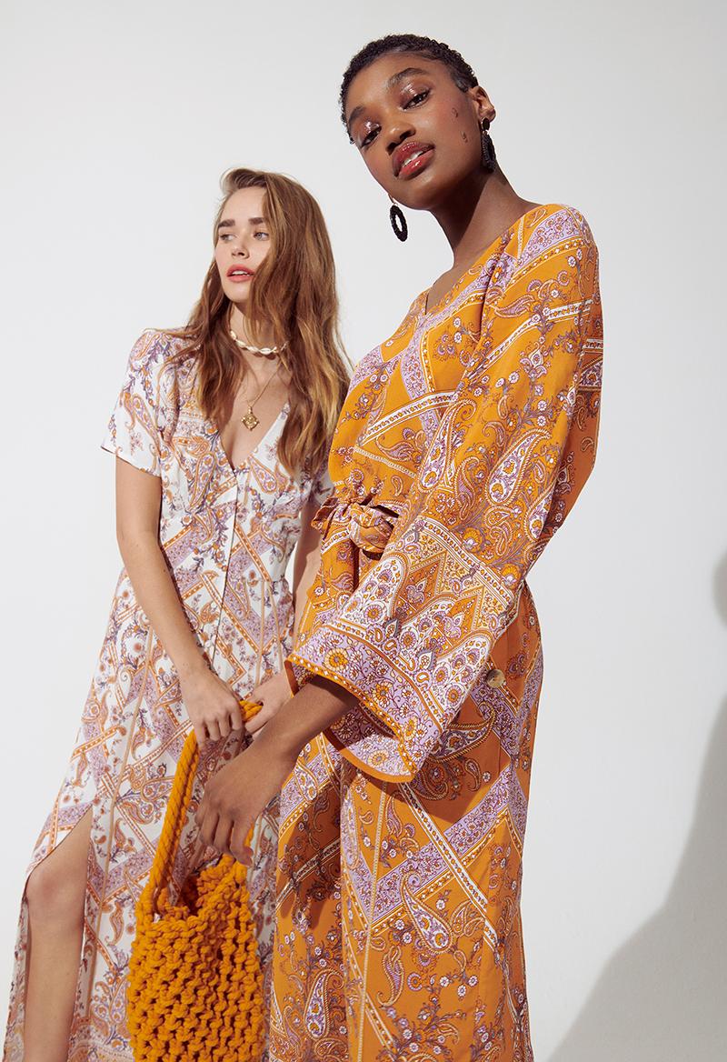 zwei junge frauen mit paisley muster kleidern