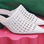 weiße geflochtene schuhe auf pinkfarbenem hocker