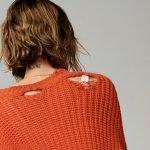 junge frau von hinten mit zerschlissenem pullover