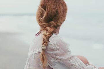junge frau mit geflochtenem zopf am strand sitzend