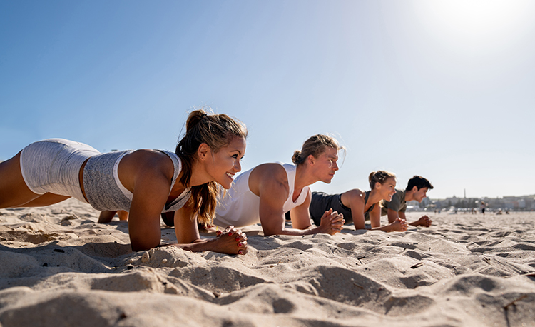 gruppe von jungen leuten trainiert am strand