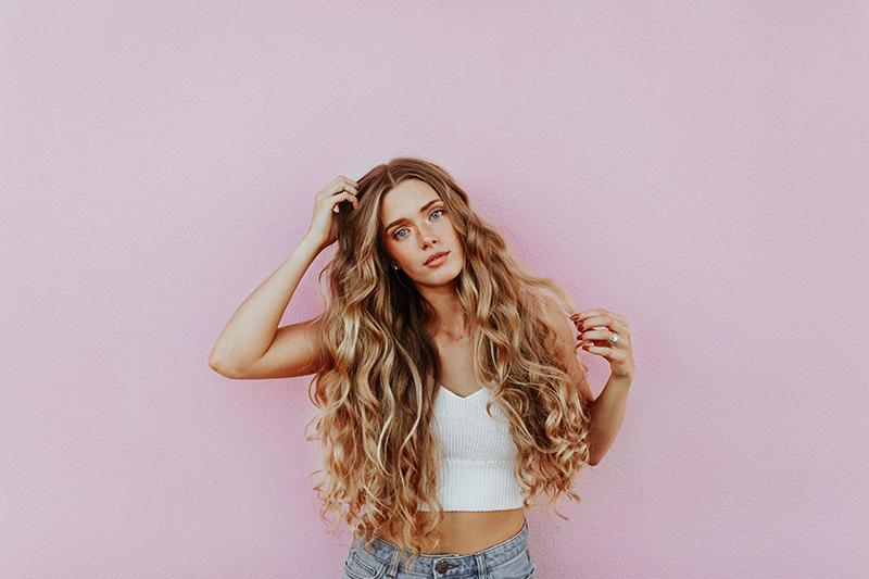 junge frau mit langen blonden gelockten haaren