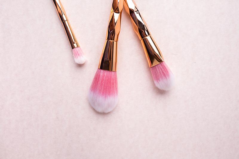 drei pinsel auf rosafarbenem untergrund
