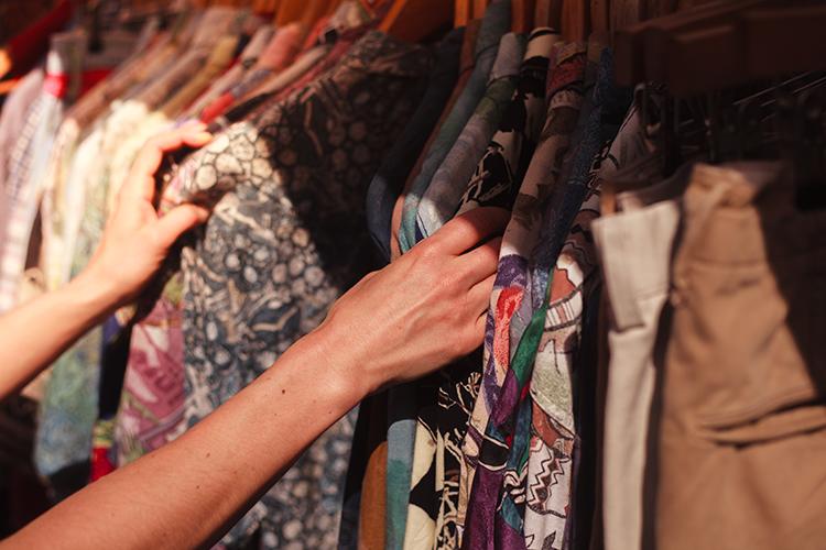 frau durchsucht kleiderstange