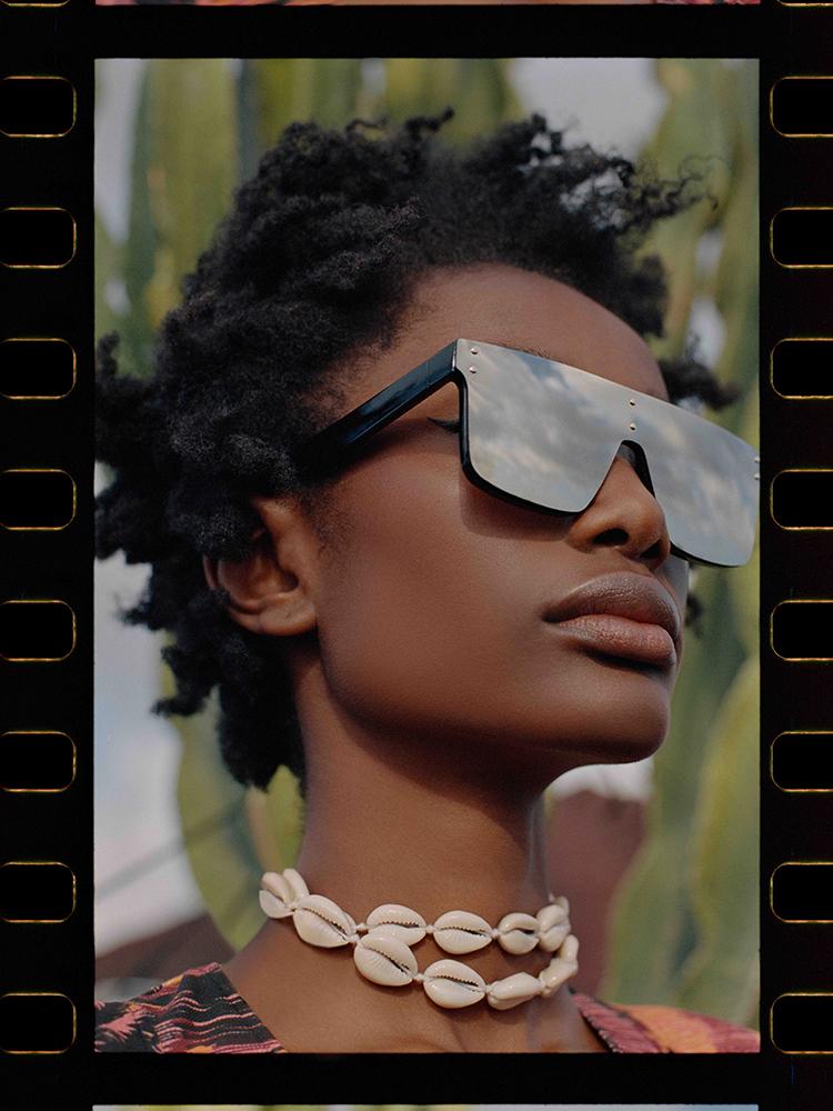 frau mit sonnenbrille und muschelkette