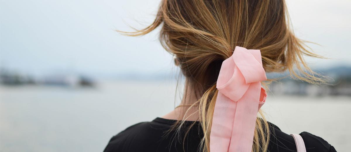 frau von hinten mit zopf und rosa haarband