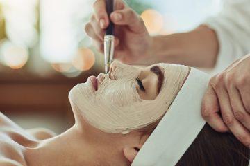 junge frau mit gesichtsmaske bei der kosmetikerin