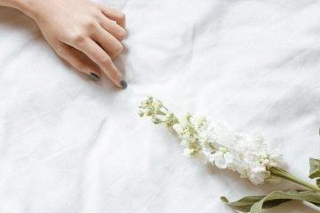 hand und blume auf weißem bettlaken