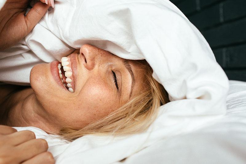 portrait einer jungen frau die lächelnd im bett erwacht