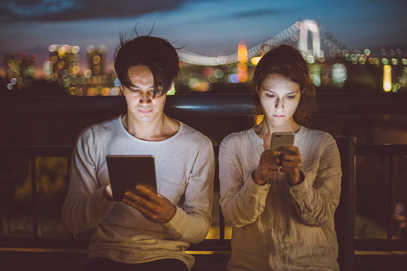 mann und frau nebeneinander sitzend mit smartphones