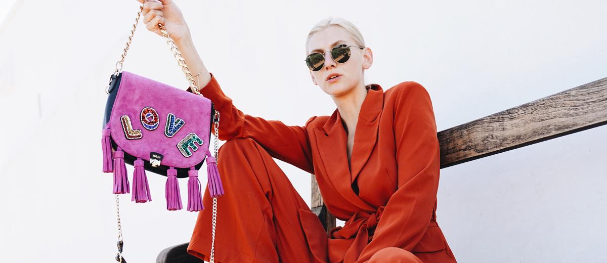 junge frau im roten anzug mit pinkfarbener tasche