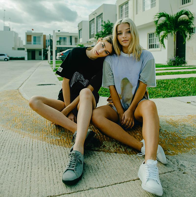 zwei junge frauen mit senakern auf boden sitzend