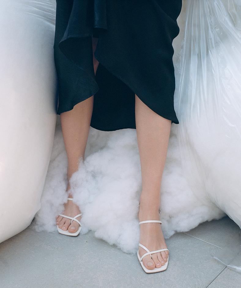 beine einer frau mit weißen sandalen