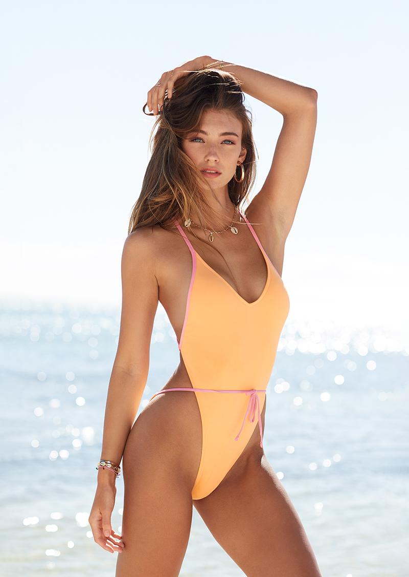junge frau am strand im apricotfarbenen high-leg-badeanzug