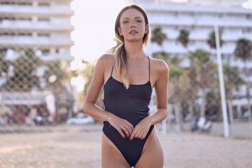 junge frau am strand im schwarzen badeanzug