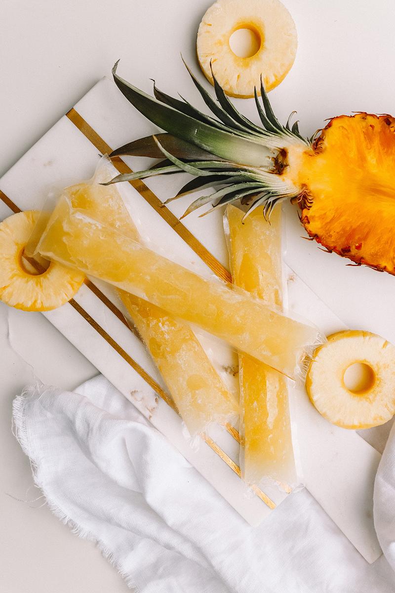 ananas mit ananasscheiben und eis auf tisch liegend