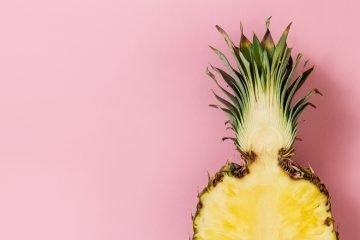halbierte ananas auf rosafarbenem untergrund
