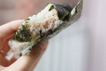 frau hält rin japanischen snack in der hand