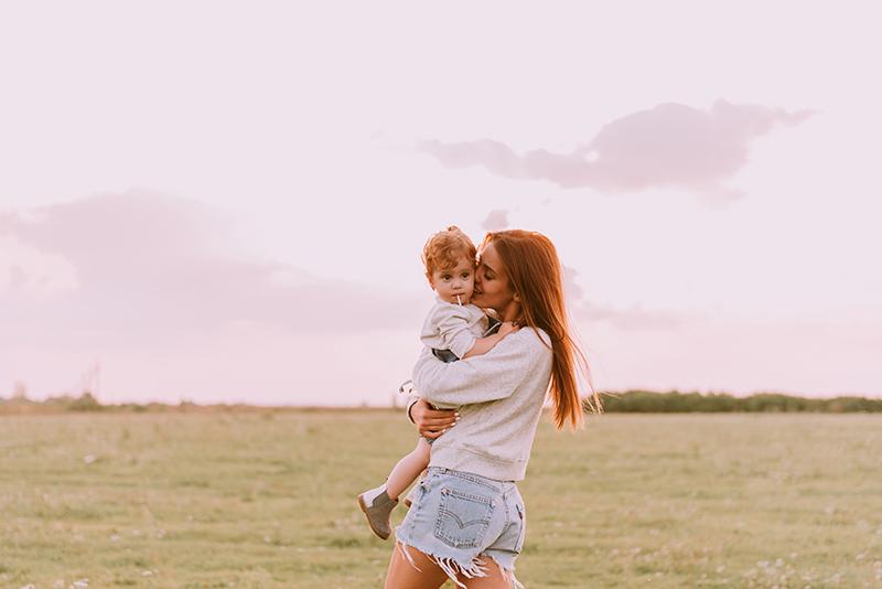 junge mutter mit kleinem kind auf dem arm