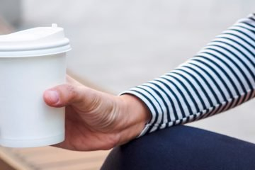 hand mit coffee to go becher