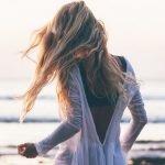 junge frau mit langen blonden haaren am strand