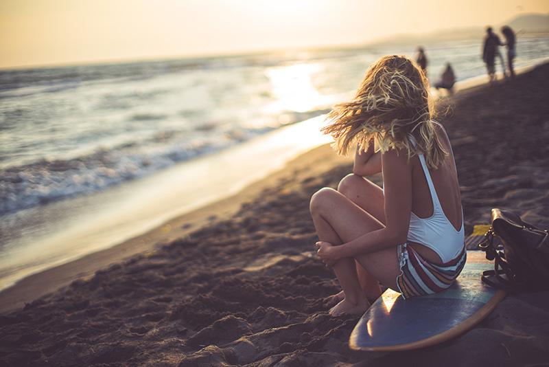 junge frau am strand auf surfbrett sitzend