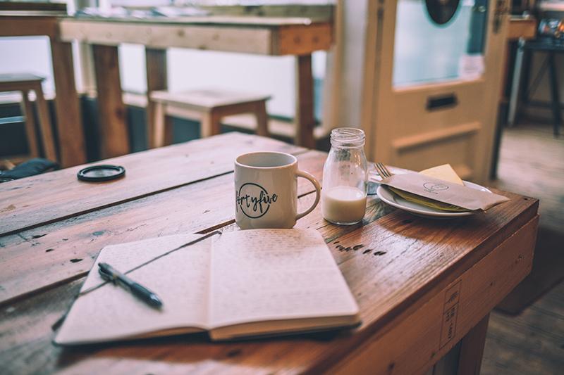 tisch mit kaffeetasse und schreibblock