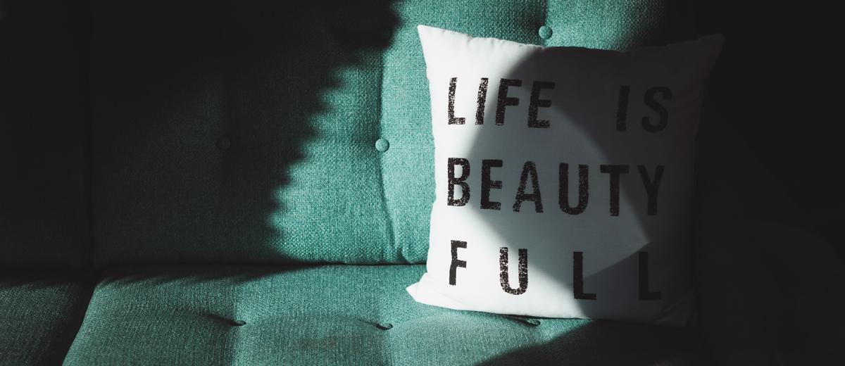 weißes kissen mit aufschrift auf grünem sofa
