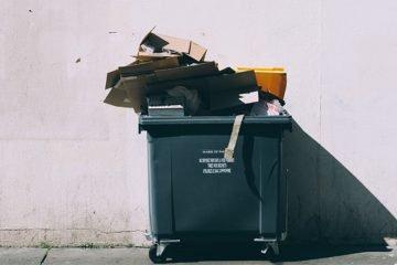 Schwarze Tonne, die mit Müll gefüllt ist