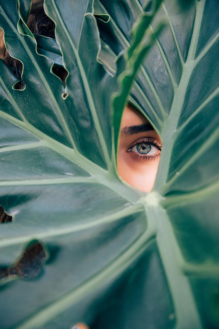 Frau schaut durch Grüne blätter