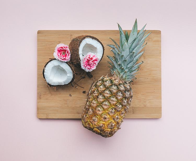 Ananas und Kokosnuss liegen auf Holzbrett vor rosa Hintergrund