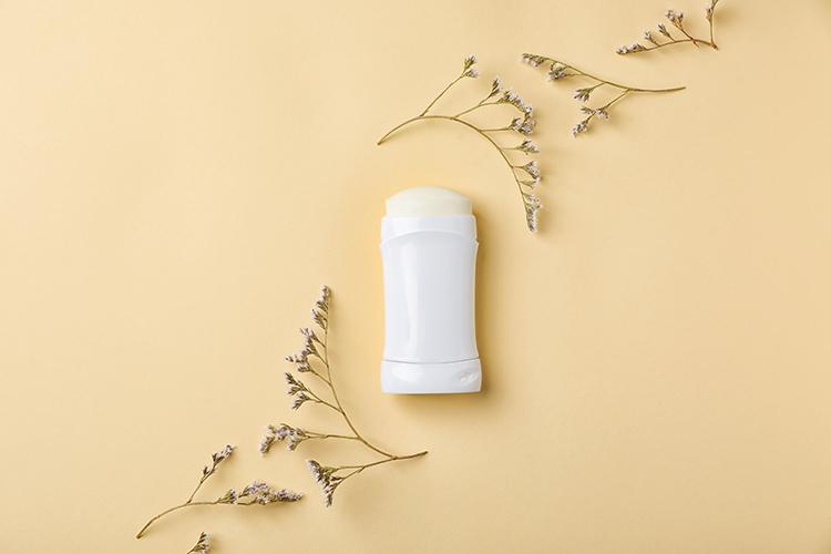 Deo ohne Aluminium vor gelber Wand und Blüten