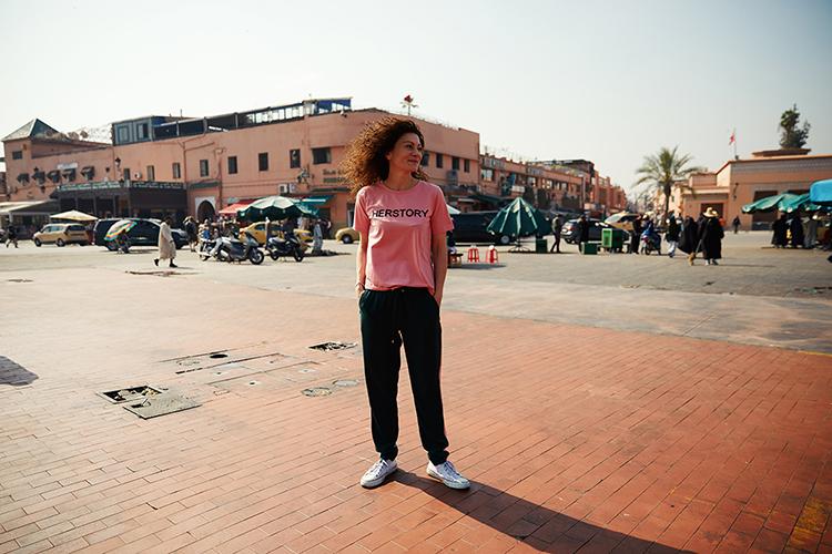 Frau mit pinkem Tshirt und schwarzer Hose steht neben Straße in Marrakesch