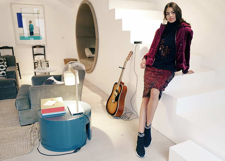 Frau mit dunkelroter Jacke lehnt an Treppe neben Gitarre