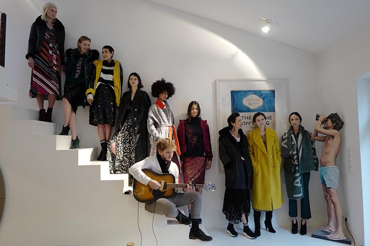 Gruppe von Frauen stehen auf Treppe und werden von Mann in Boxershort fotografiert