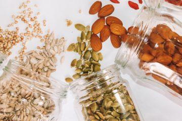 Gläser mit Samen gefüllt liegen auf hellem Untergrund