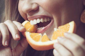 Frau beißt in Orangenscheibe