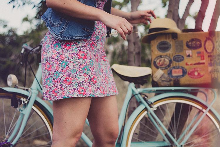 Frau in Sommerkleid vor hellblauem Fahrrad