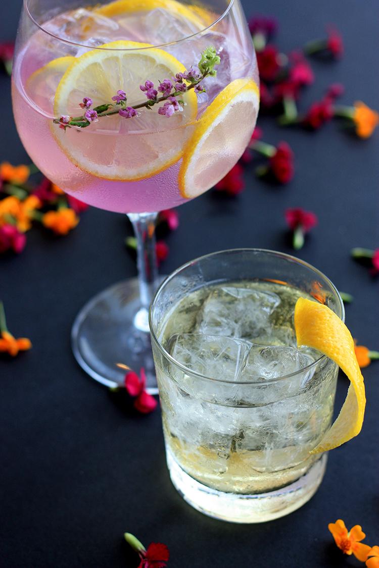 Zwei gefüllte Gläser gefüllt mit rosafarbenem Getränk und Zitronenscheiben und Blüten