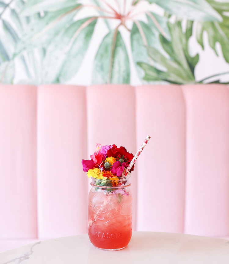 Getränk mit Blumenstrauß im Glas vor rosafarbenem Sofa
