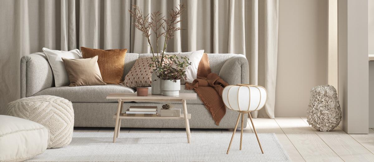 Beiges Sofa mit Kissen vor beigem Vorhang