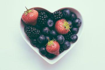 Herzförmige Obstschale gefüllt mit Erdbeeren, Heidelbeeren und Himbeeren